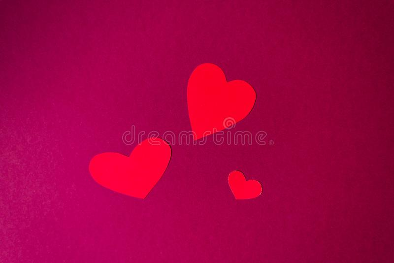 Three hearts of different sizes on a bright pink background with copying space. Pattern for Valentine`s day. Holiday card for the royalty free stock photo