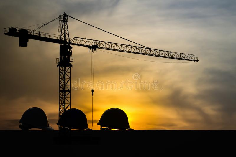 Three helmet silhouette at construction site with crane background and sunset.  royalty free stock photography