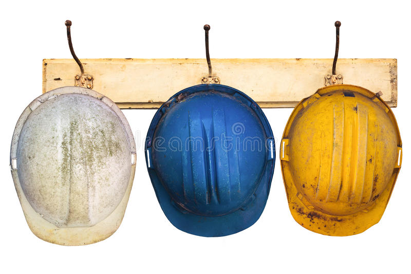 Three helmets hanging on a hat-rack stock image
