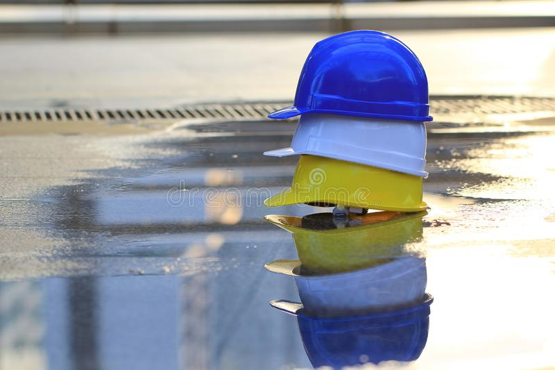 Three helmets yellow, white and blue on concrete floor and water background. Safety and Construction concept stock photo
