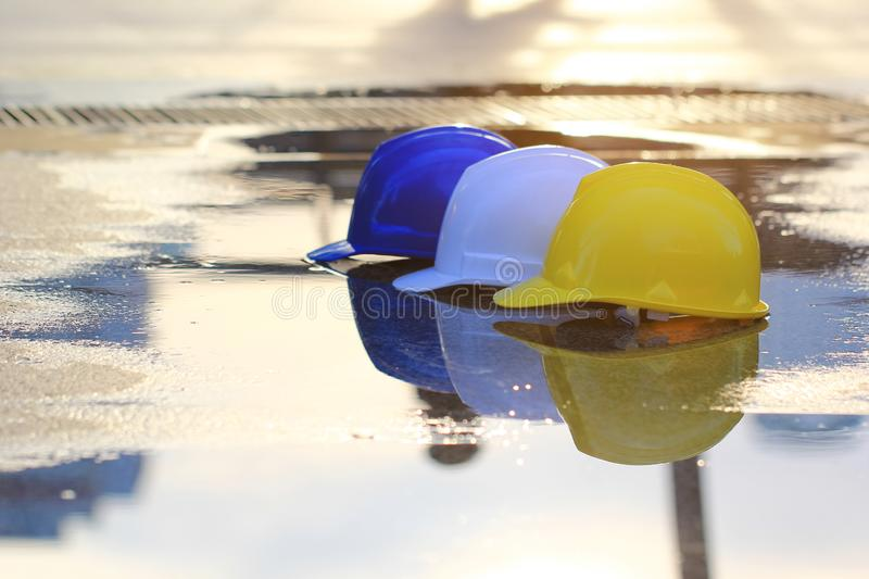 Three helmets yellow, white and blue on concrete floor and water background. Safety and Construction concept stock photography