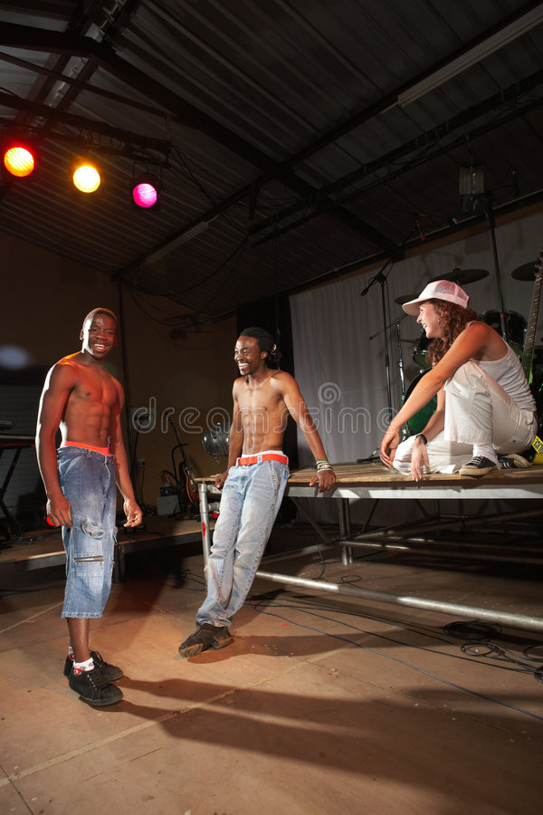 Three hip-hop dancers. Three freestyle hip-hop dancers standing around after a training session. Two young adult males and a female in a home training studio stock photography