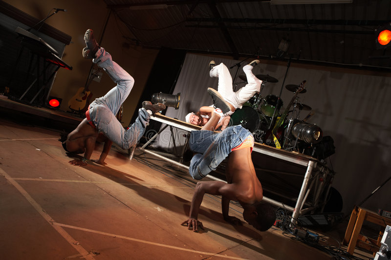Three hip-hop dancers. Three freestyle hip-hop dancers in a dancing training session. Two young adult males and a female in a home training studio with stage and royalty free stock photography
