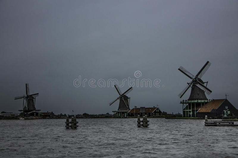 Three historic windmills on a cloudy day royalty free stock images