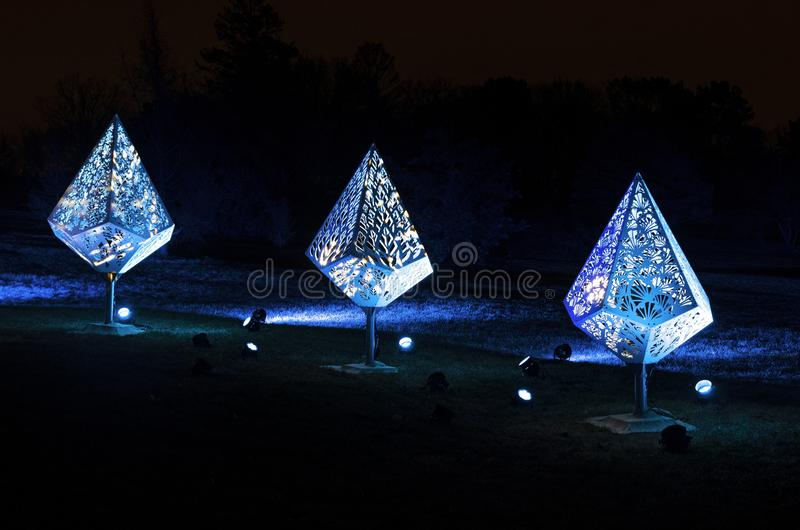 Three Holiday Fixtures in Blue Glow. Three holiday fixtures illuminated by blue colored floodlights at night in park royalty free stock photos