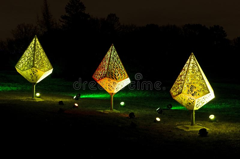 Three Holiday Fixtures Glow at Night. Holiday fixtures lit by colored floodlights at night during holiday celebration in park stock photo