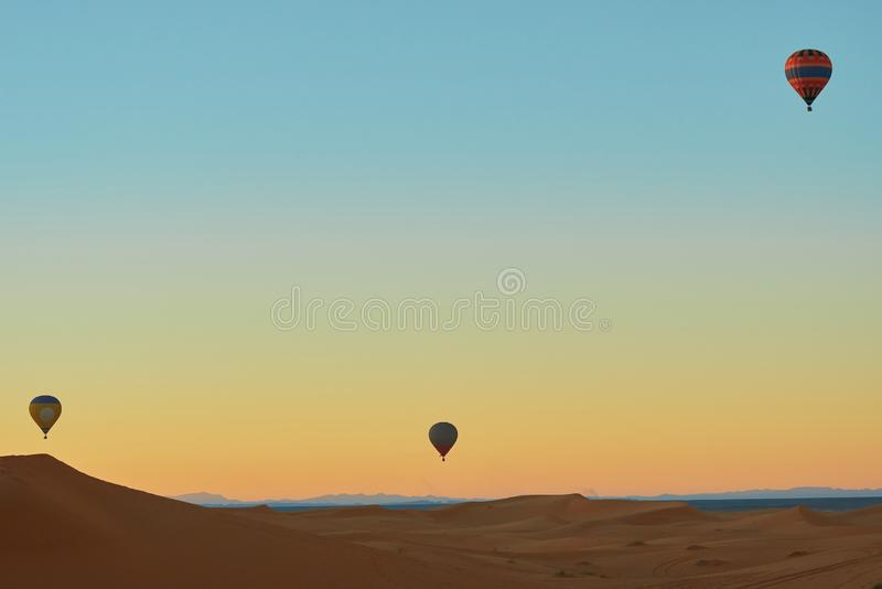 Three hot air balloon flying over the desert stock photo