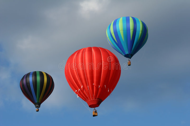 Three hot air balloons. In the cloudy blue sky royalty free stock photo