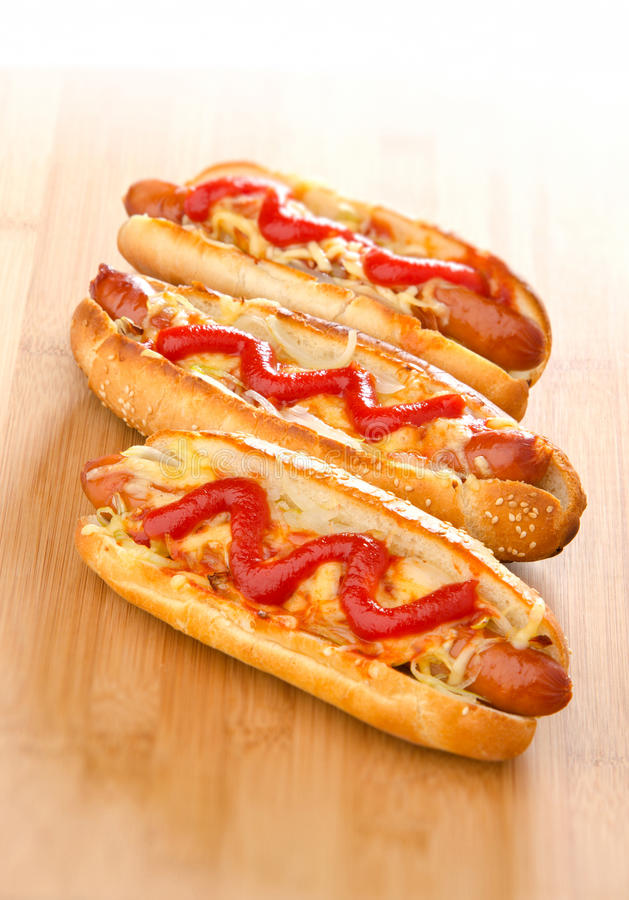 Hot dog. Three hot dogs on a wooden board royalty free stock images