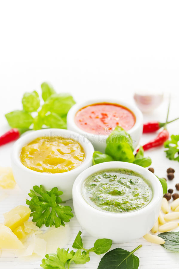 Three hot sauces. Assortment of three colorful hot sauces with ingredients stock photos
