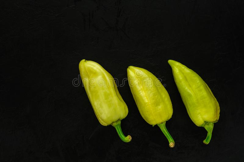 three hot yellow-green peppers in a row on a background of black concrete textured plaster. Creative layout template with space stock photo