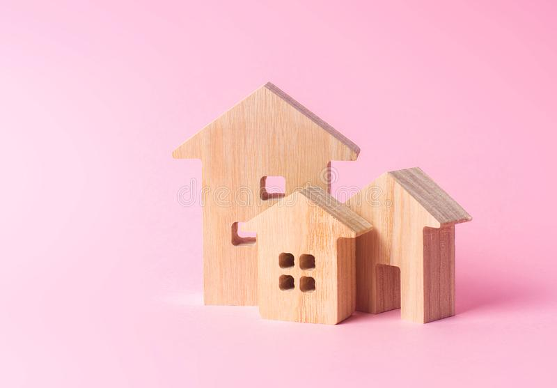 Three houses on a pink background. Buying and selling of real estate, construction. Apartments and residential buildings in a city. Or settlement. Investments stock photos