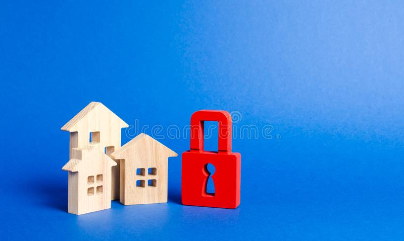 Three houses and a red padlock. Unavailable and expensive real estate. house Insurance. Security and safety. Confiscation. For debts. alarm system. seizure of royalty free stock photo