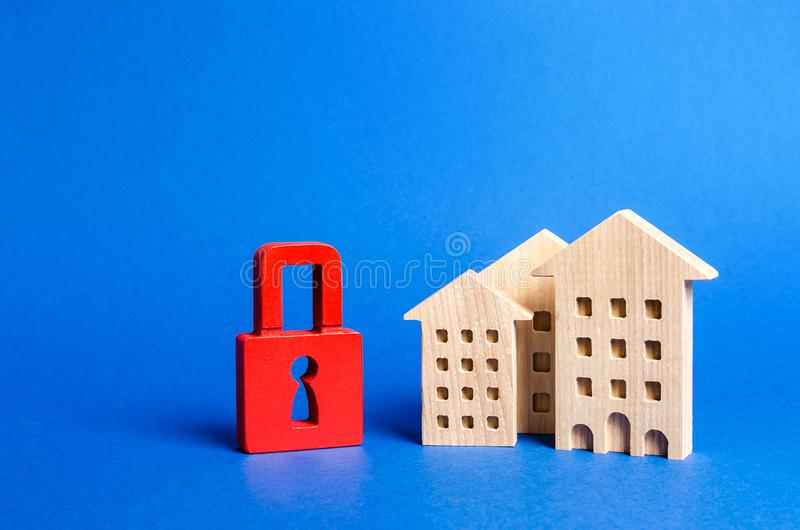 Three houses and a red padlock. Unavailable and expensive real estate. house Insurance. Security and safety. Confiscation. For debts. alarm system. seizure of royalty free stock image