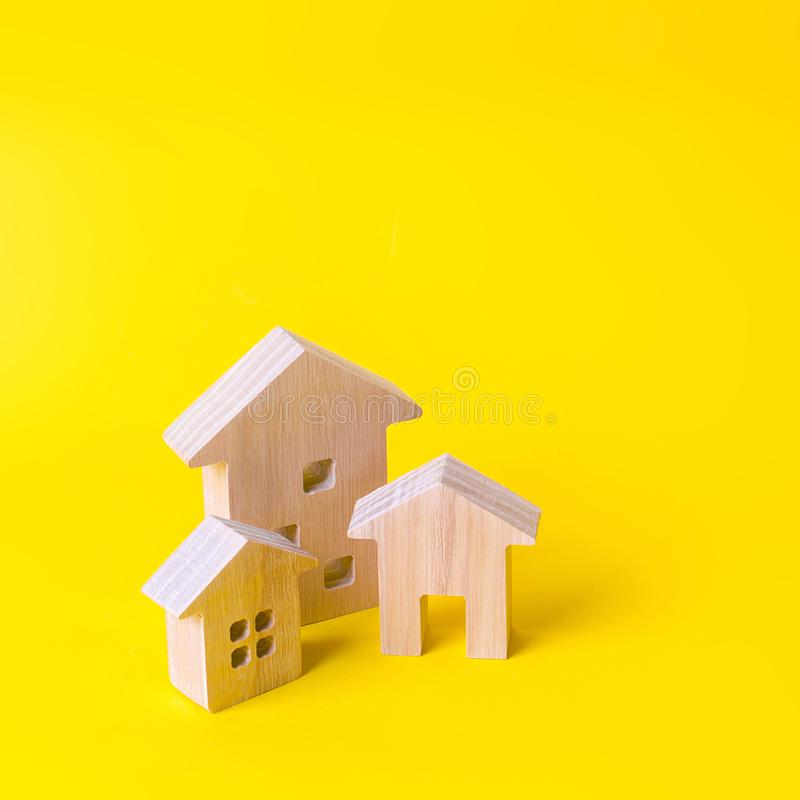 Three houses on a yellow background. Buying and selling of real estate, construction. Apartments and residential buildings. In a city or settlement. Investments stock image