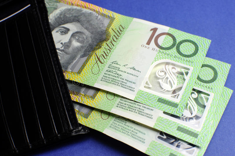 Three hundred Australian dollar notes with wallet. Three hundred Australian dollar green and yellow notes folding out from black wallet royalty free stock photography