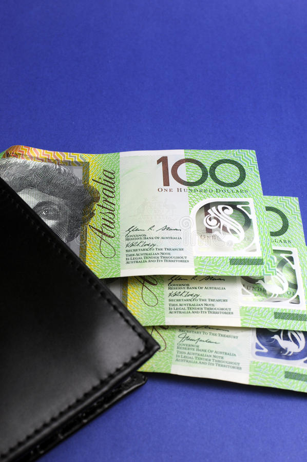 Three hundred Australian dollar notes with wallet - vertical. Three hundred Australian dollar green and yellow notes folding out from black wallet stock image
