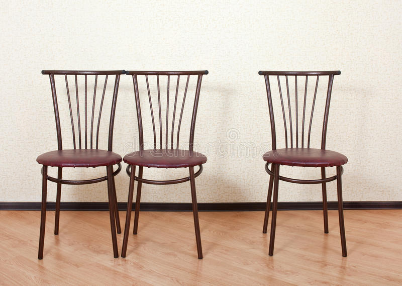 Three identical chair next against the wall. Three identical chair next to the wall standing in an empty room royalty free stock images