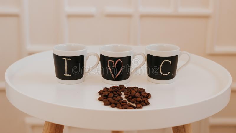 Three identical small coffee cups in a row standing on white round wooden table. With text I love coffee stock image