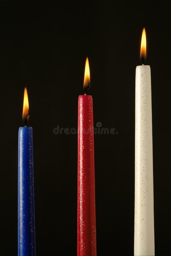 Three ignited wax candles royalty free stock photo