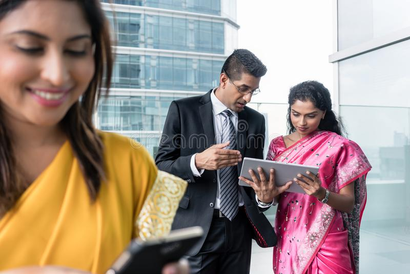 Three Indian business people using modern devices indoors stock photo