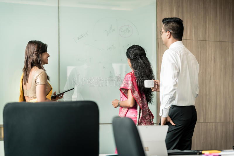 Three Indian colleagues writing ideas during brainstorming stock photo