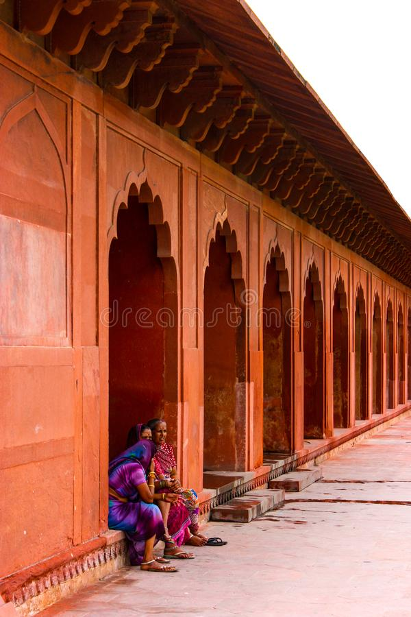 Agra, India - August 19, 2009: three Indian women chat sitting under the arches near the Taj Mahal in Agra, India stock photography
