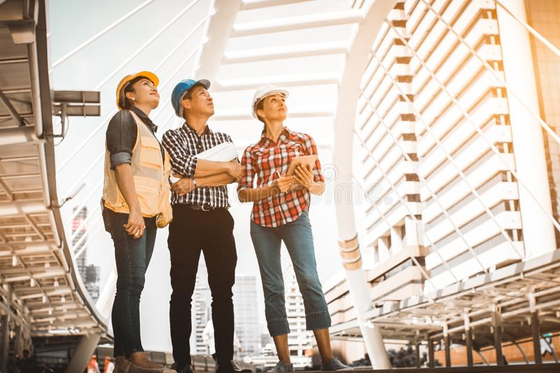 Three industrial engineer standing and looking to right side wear safety helmet with holding inspection and digital tablet. On building outside. Engineering stock photography