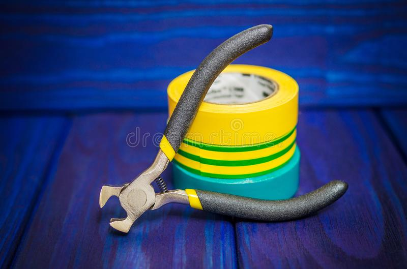 Three insulating tape and pliers for electrician on blue wooden boards stock photography