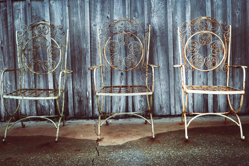 Three iron chairs. Vintage and rusting chairs sit by a wood pannelled shed stock photo