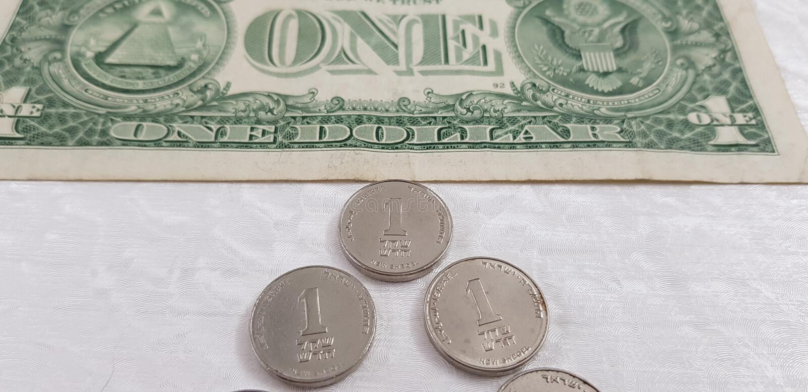 Three Israeli sheckel coins on white background near american dollar banknote stock photos