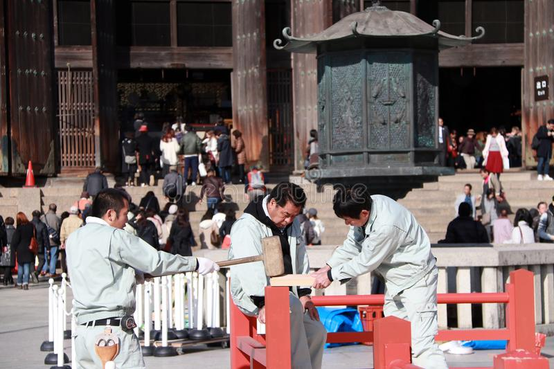 Three Japanese carpenter are construction the stage, Using a wooden hammer strike to the components of the stage. royalty free stock image