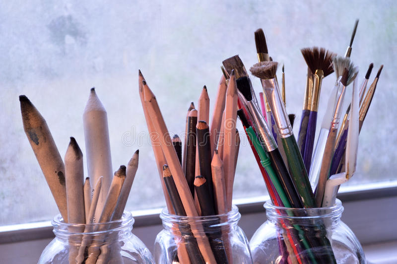 Three jars with fine art tools. Paintbrushes, pencils and tortillons. Painting,drawing and sketching tools. Graphite and charcoal pencils for fine art in the royalty free stock photo