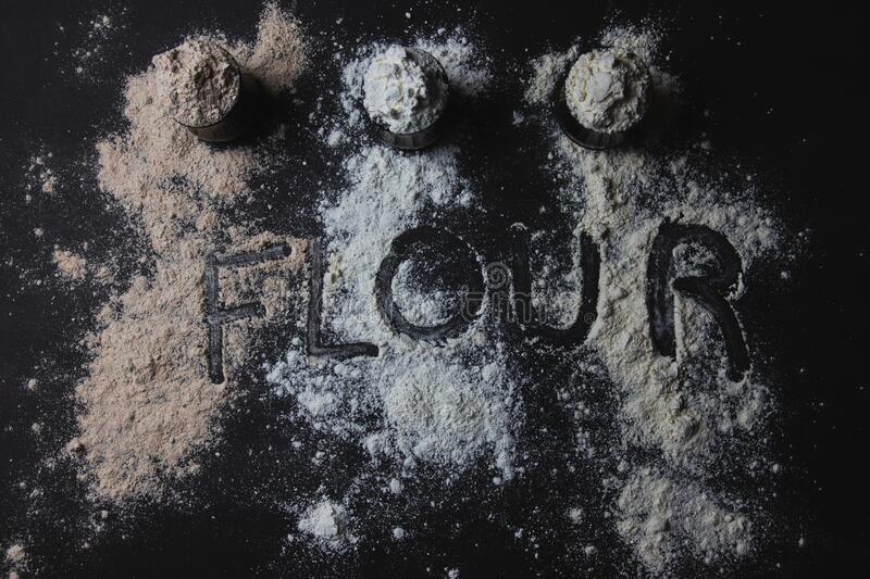 Three jars full of different types of flour, gluten free alternatives, sprinkled flour, and the word flour written. On top royalty free stock image