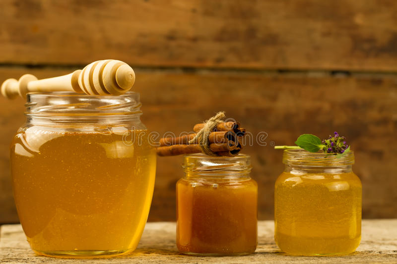 Three jars of honey with drizzler, cinnamon, flowers on wooden background. Jars of honey with drizzler, cinnamon, flowers on wooden background stock image