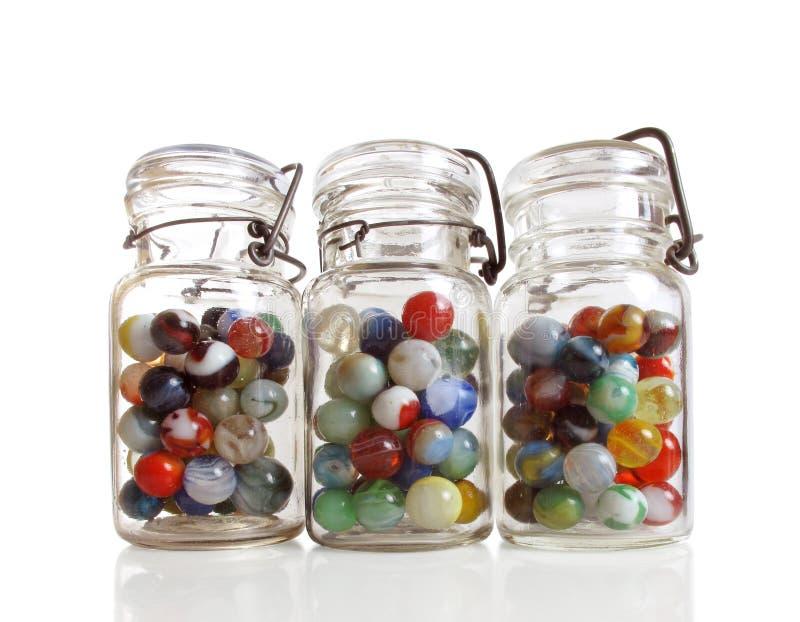 Three jars of marbles stock image