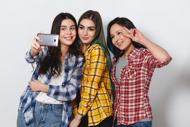 Three joyful girls girlfriends are doing selfie. smiling. light gray background royalty free stock photography