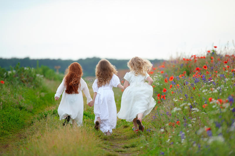 Three kid girls in white dresses running out outdoors. Playing c. Hildren royalty free stock image