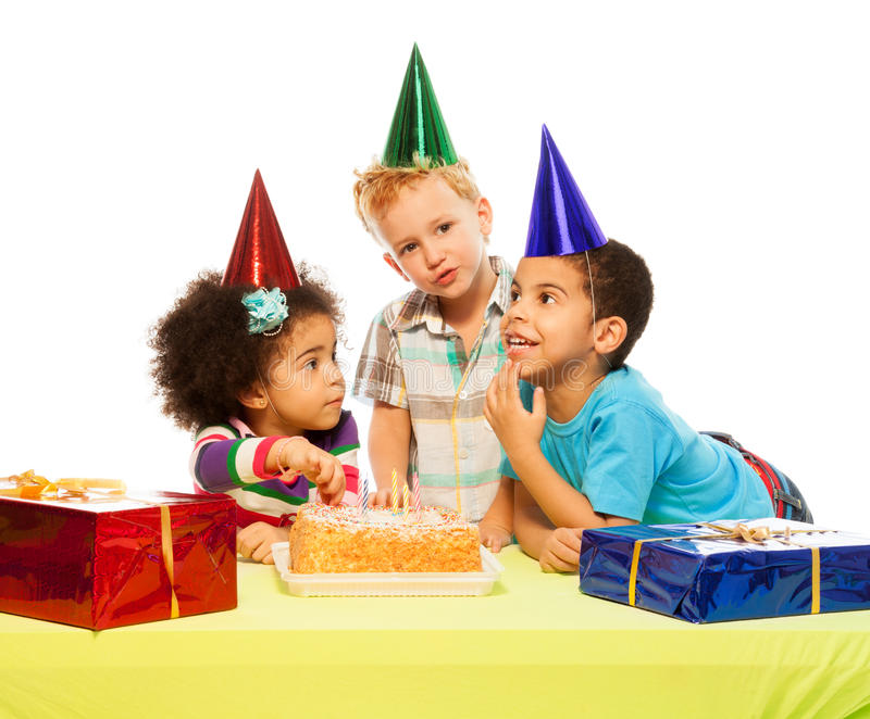 Three kids and birthday cake. Three kids sitting by the table with presents and birthday cake royalty free stock image