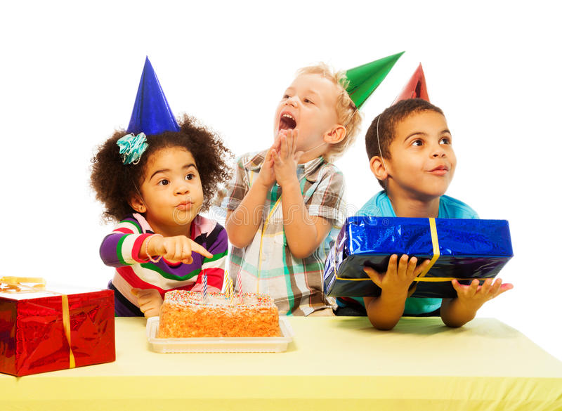Three kids with birthday cake and peresents. Three kids with different appearance sitting by the table with presents and birthday cake royalty free stock photography
