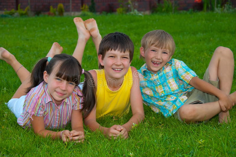 Three kids on grass. A group of three happy kids, sister and brothers resting on green grass royalty free stock images