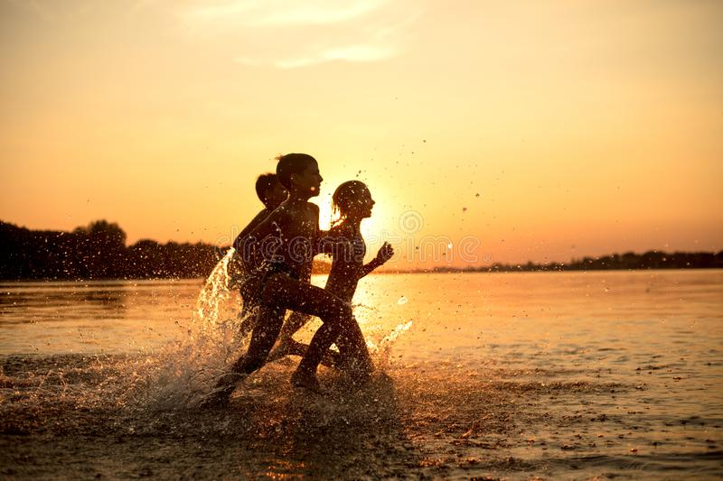 Happy children playing on the beach at the sunset time. Three Kids having fun outdoors. Concept of summer vacation and friendly family stock image