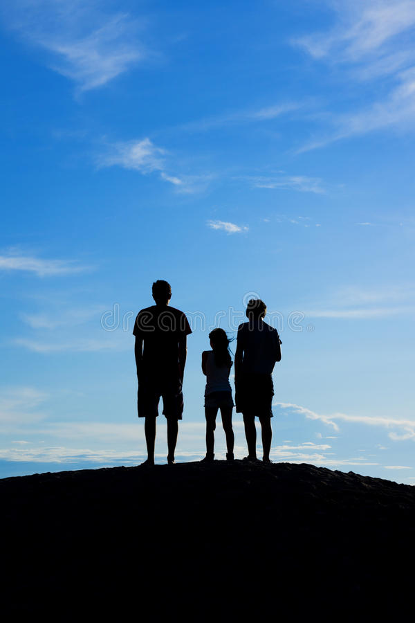 Three kids on a hill stock photo