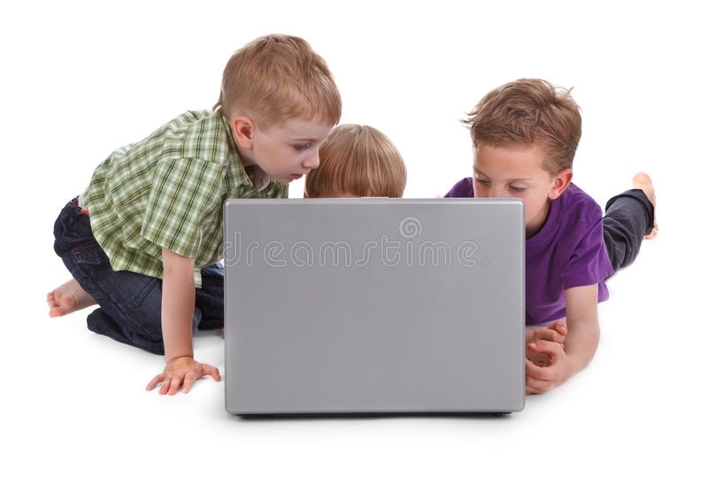 Three kids with laptop. Studio shot of three kids with laptop royalty free stock images