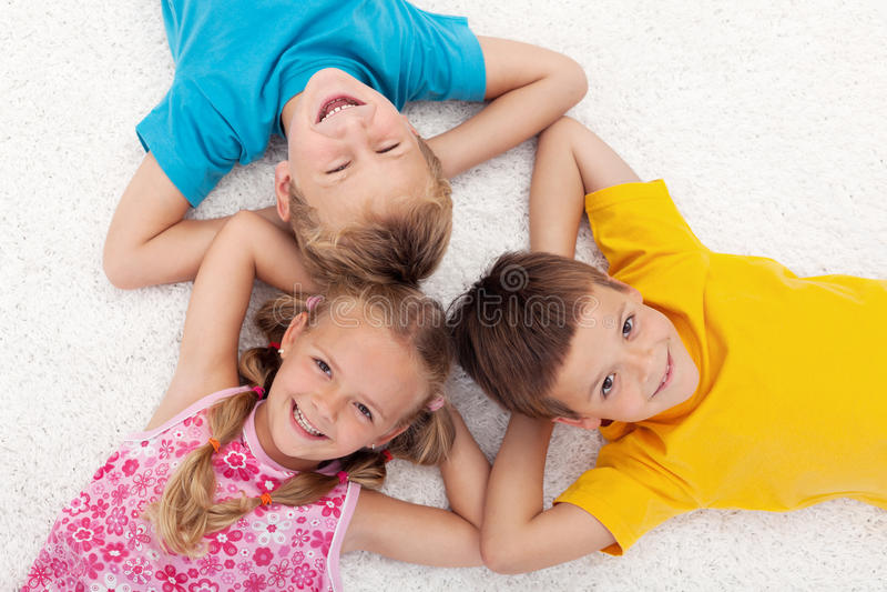 Three kids laying on the floor in circle. Three happy kids laying on the floor in circle laughing stock photo
