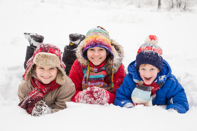 Three kids lying down together on winter snow stock photography