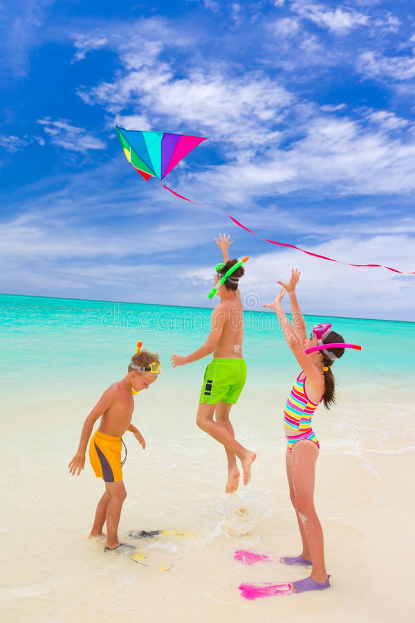 Three kids playing on beach royalty free stock photo