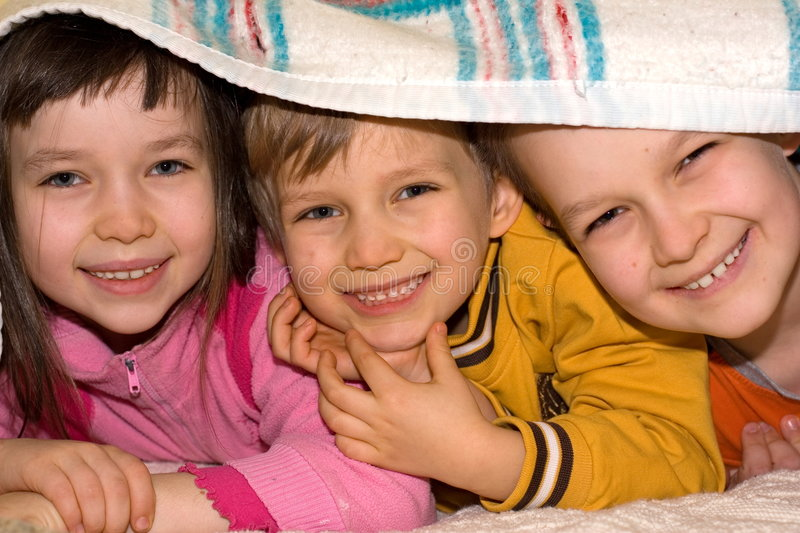 Three Kids Playing at Home. Three happy kids peek out from under a blanket where they have been hiding royalty free stock photo