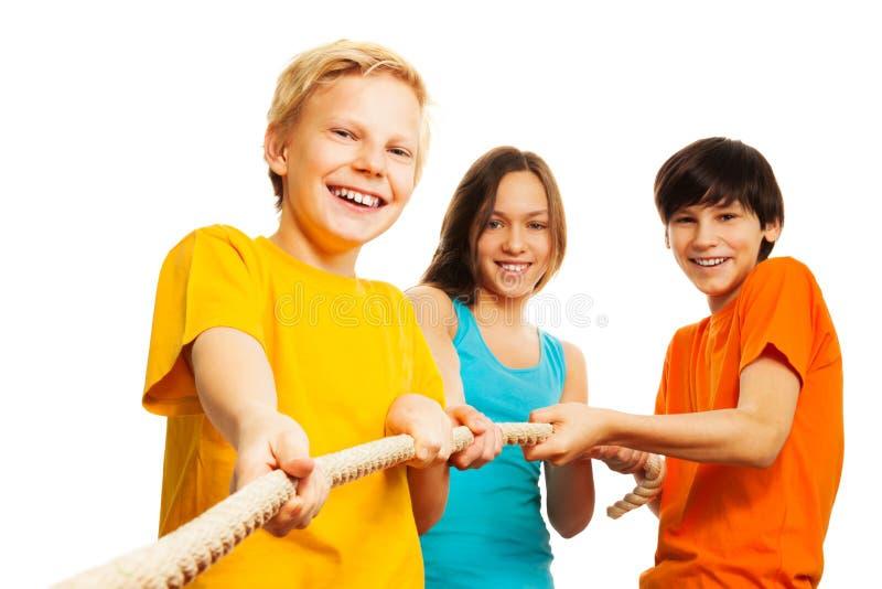 Three kids pull the rope stock photos