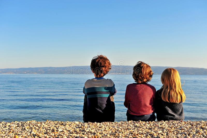 Three kids sitting on the beach royalty free stock photo